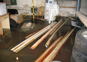 A severely flooding basement in Cookeville, with lumber and personal items floating in a foot of water